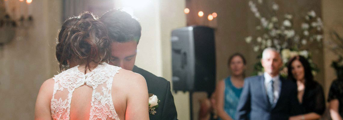 Beautiful couple sharing their first dance as family & friends look on