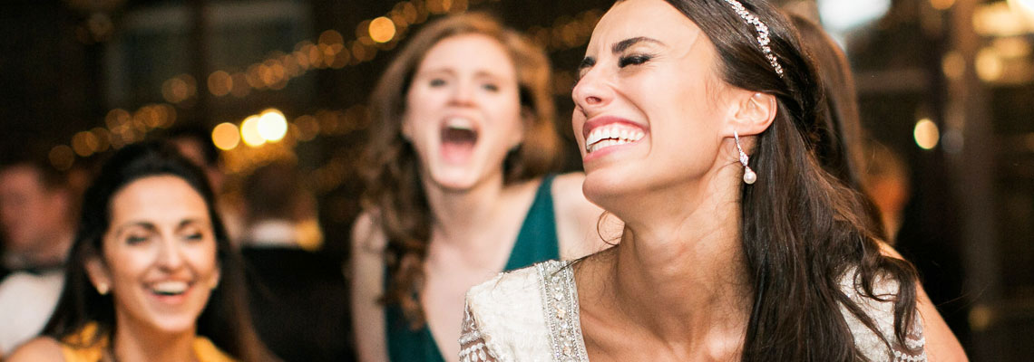 Smiling bride laughing with friends while the band plays at her wedding